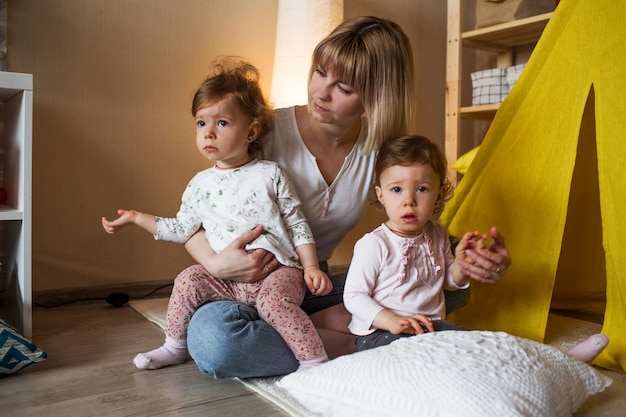 Een gelukkige moeder met twee tweelingmeisjes speelt thuis op de vloer die dichtbij een gele tipi zit. gezamenlijke spelletjes van moeders en dochters.
