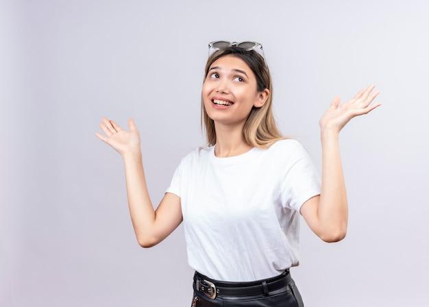 Een gelukkige mooie jonge vrouw in een wit t-shirt draagt een zonnebril op haar hoofd en denkt en heft haar handen in geluk op een witte muur