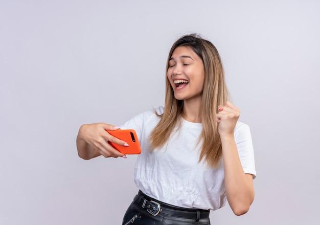 Een gelukkige mooie jonge vrouw in wit t-shirt die gebalde vuist opheft terwijl ze mobiele telefoon met gesloten ogen op een witte muur houdt Gratis Foto