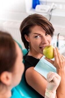 Een gelukkige patiënt bij de receptie van de stamatoloog, controleert de gezondheid van de tanden, bijt groene appels. tandheelkunde concept, gezonde tanden, mooie glimlach.