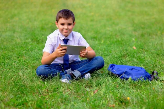 Een gelukkige schooljongen in een wit overhemd en een blauwe band zit op groen gras en houdt een tablet vast. kopieer ruimte.