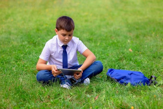 Een gelukkige schooljongen in een wit overhemd en een blauwe das zit op groen gras en speelt een tablet. kopieer ruimte.