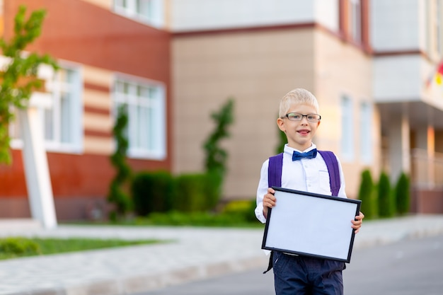 Een gelukkige schooljongen met een blonde bril en een rugzak staat op de school en houdt een bord met een wit laken vast. dag van de kennis.