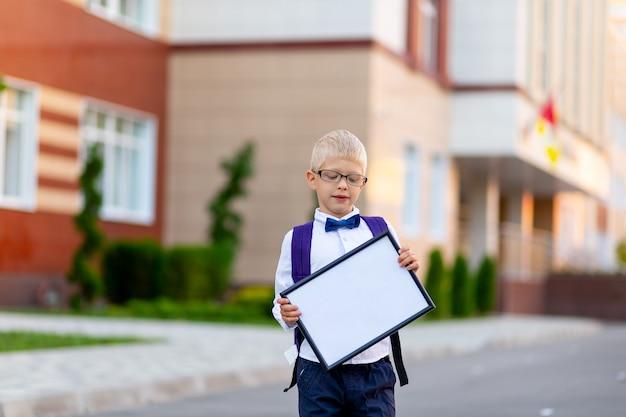 Een gelukkige schooljongen met een blonde bril en een rugzak staat op de school en houdt een bord met een wit laken vast.