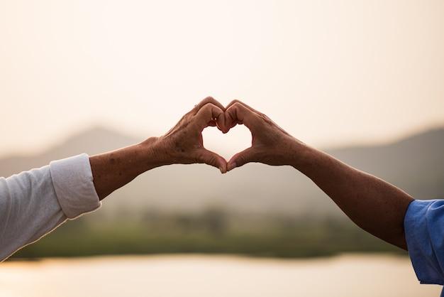 Een gelukkige senior paar aziatische oude man en vrouw met hart teken