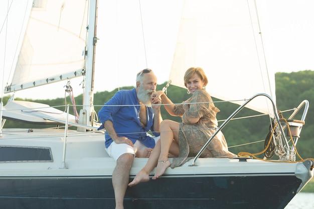 Een gelukkige senior paar zeilen en zitten achter het stuur van een zeilboot op meer.
