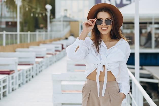 Een gelukkige stijlvolle vrouw loopt langs het strand op een warme zomerdag in de zonsondergang