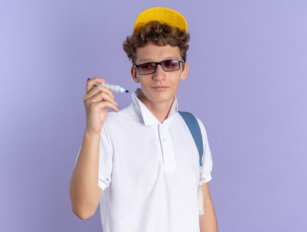 Een gelukkige student in een wit poloshirt en een gele pet met een bril met een rugzak die een pen vasthoudt en ernaar kijkt met een glimlach op het gezicht