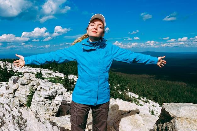 Een gelukkige toeristenreiziger die in de bergen staat met zijn handen omhoog