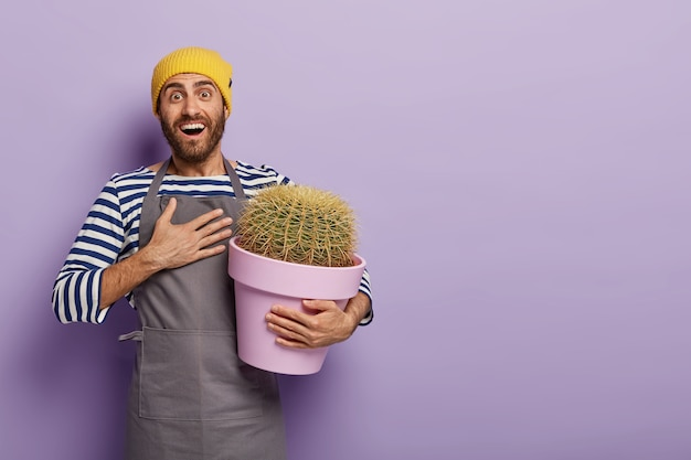 Een gelukkige tuinman is een vriend dankbaar dat hij een nieuw soort cactussen in zijn tuincollectie heeft gekregen, houdt de hand op de borst