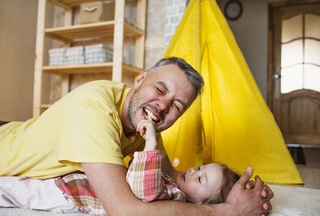 Een gelukkige vader bijt de vinger van zijn dochtertje terwijl hij thuis samen op de grond speelt. gezamenlijke spelletjes van de vader met het kind