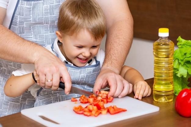 Een gelukkige vader en een jonge zoon bereiden in de keuken een salade met groenten.