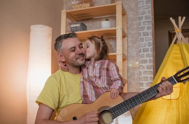 Een gelukkige vader heeft een gitaar in zijn handen. een klein meisje kust haar vader op de wang. een zorgzame vader