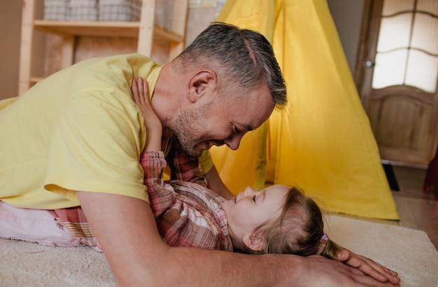 Een gelukkige vader ligt op de grond naast zijn dochtertje en kijkt elkaar aan. het concept van gezinsgeluk