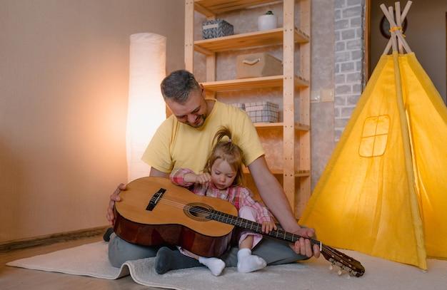 Een gelukkige vader met een dochtertje leert gitaar spelen terwijl hij thuis op de grond bij de gele tipi zit. gelukkige vader