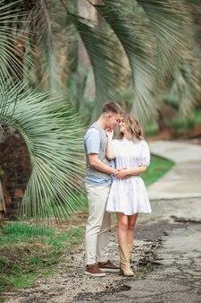 Een gelukkige verliefde paar lopen in het park onder palmbomen, hand in hand.