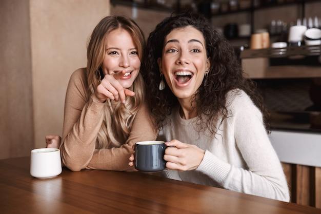 Een gelukkige vriendinnen die in café zitten en met elkaar praten en thee of koffie drinken wijzend