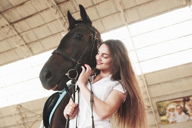 Een gelukkige vrouw communiceert met haar favoriete paard. de vrouw houdt van dieren en paardrijden