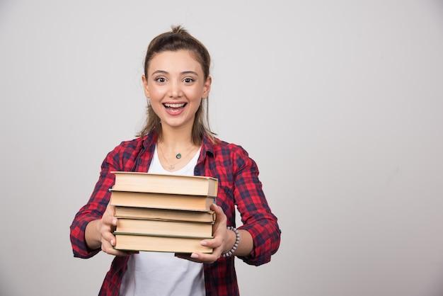 Een gelukkige vrouw die een stapel boeken op een grijze muur draagt.