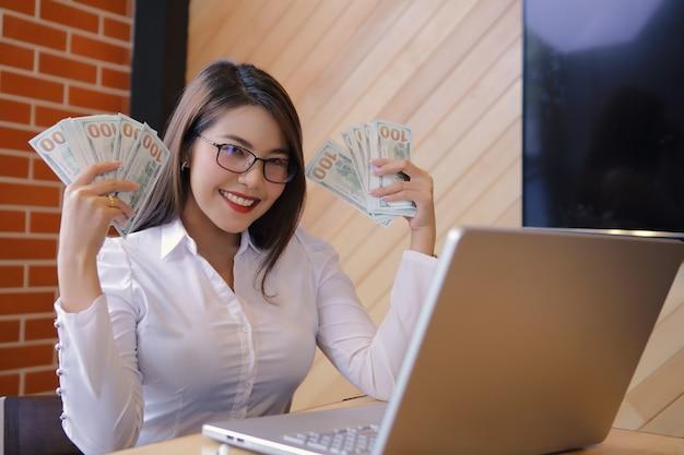 Een gelukkige vrouw draagt dollars terwijl het gebruiken van een laptop. ze slaagde erin te investeren.