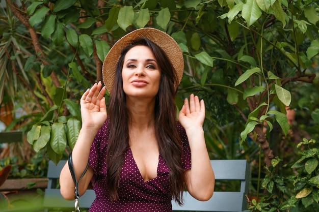 Een gelukkige vrouw in een strooien hoed zit op een bankje in een park