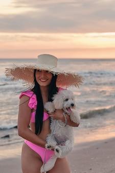Een gelukkige vrouw in roze zwempak en met een strohoed op het strand met haar puppy