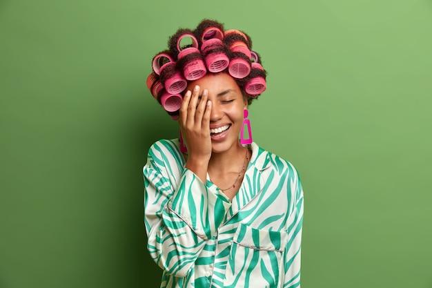 Een gelukkige vrouw met een donkere huid maakt gezicht handpalm, kan niet stoppen met lachen na het horen van een grap, drukt positieve emoties uit, draagt haarkrulspelden om er fantastisch uit te zien op het feest van morgen, gekleed in een zijden jurk. haarstylen