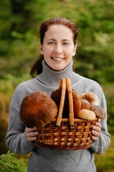 Een gelukkige vrouw met een mand met paddenstoelen in het bosportret van een boswachter met een oogst