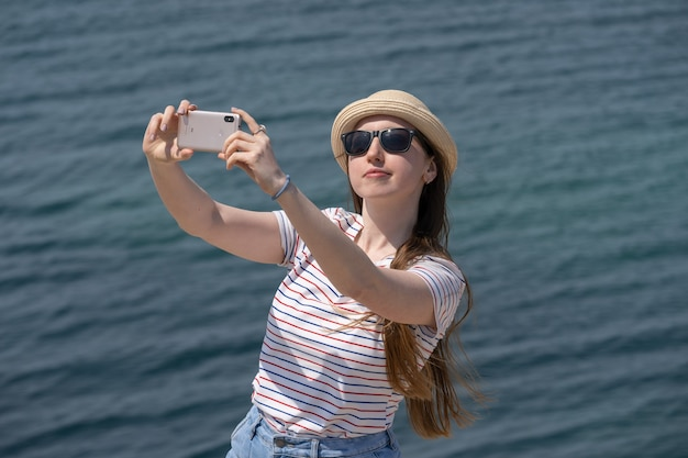Een gelukkige vrouw met een strohoed en zonnebril filmt zichzelf terwijl ze de telefoon gebruikt tegen de achtergrond van de eindeloze zee en de blauwe lucht. frisse zeelucht. vakantie in het buitenland.