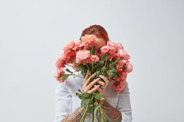 Een gelukkige vrouw met een tatoeage op haar handen verbergt haar gezicht achter een boeket verse rozen in een kleur van het jaar 2019 living coral pantone. ansichtkaarten voor moederdag.