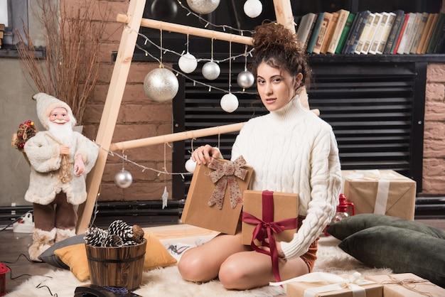 Een gelukkige vrouw met geschenkdozen met strik