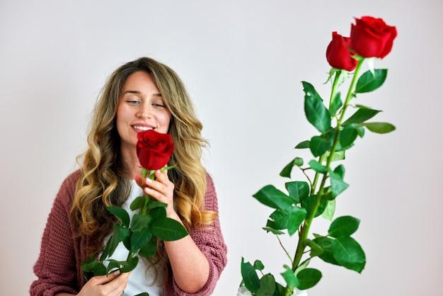 Een gelukkige vrouw met rode rozen