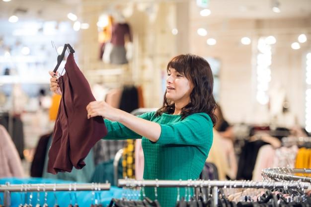 Een gelukkige vrouw vindt een mooie korte broek die te koop is in een winkelcentrum