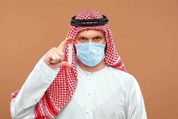 Een gemaskerde arabische man houdt een reageerbuis vast in een nationaal kostuum.