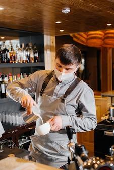 Een gemaskerde barista bereidt heerlijke koffie aan de bar in een café. het werk van restaurants en cafés tijdens de pandemie.