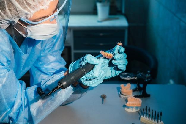 Een gemaskerde en gehandschoende tandtechnicus werkt aan een prothetische tand in zijn laboratorium.