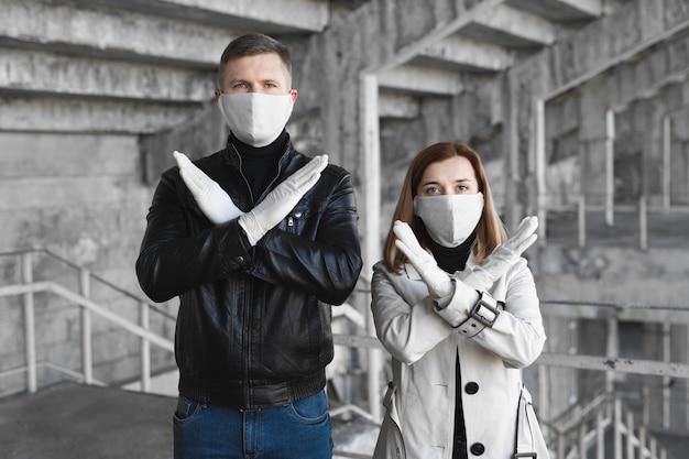 Een gemaskerde man en vrouw vertonen een stopteken voor het coronavirus. de pandemie van 2020 covid19. stop het coronavirus. quarantaine. coronavaccin