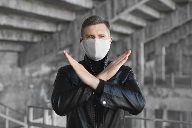 Een gemaskerde man toont een stopteken voor het coronavirus. de pandemie van 2020. stop het coronavirus. covid19. quarantaine. coronavaccin