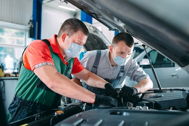 Een gemaskerde monteur controleert de auto bij het tankstation.
