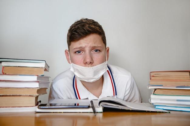 Een gemaskerde tiener thuis voor schoolboeken met een vermoeide blik