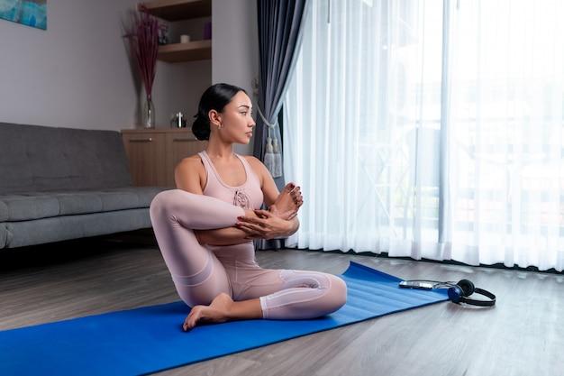 Een gemengd rasmeisje zit met haar voet voor haar borst, strepend, zittend in haar appartement op een blauw rekbaar kleed