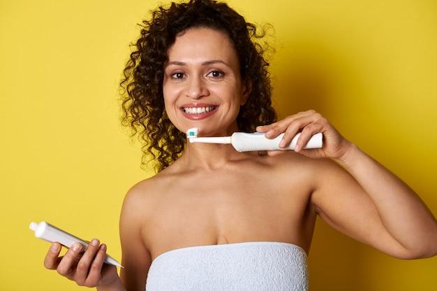 Een gemengde rasvrouw die een tandenborstel en tandpasta houdt klaar om haar tanden te poetsen die de geïsoleerde camera bekijken