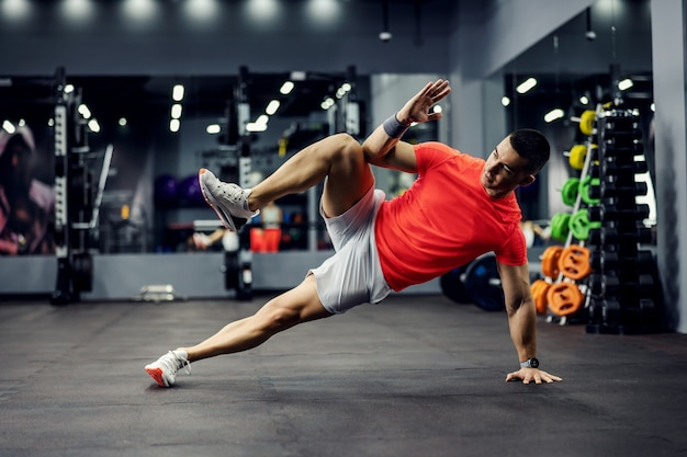 Een gemotiveerde mannelijke sporter doet een zijplank voor kern- en advertentieoefeningen met één hand en één been omhoog