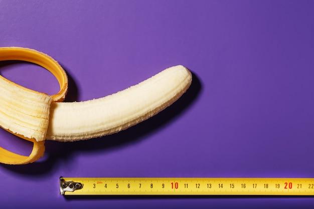 Een gepelde banaan wordt in lengte gemeten met een gele liniaal op een paarse achtergrond.