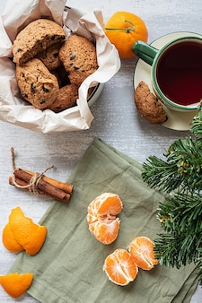 Een gepelde mandarijnchocoladekoekjes en een dennenboomtak