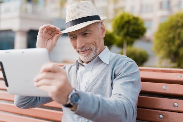 Een gepensioneerde zit op een bank in een prachtig plein.