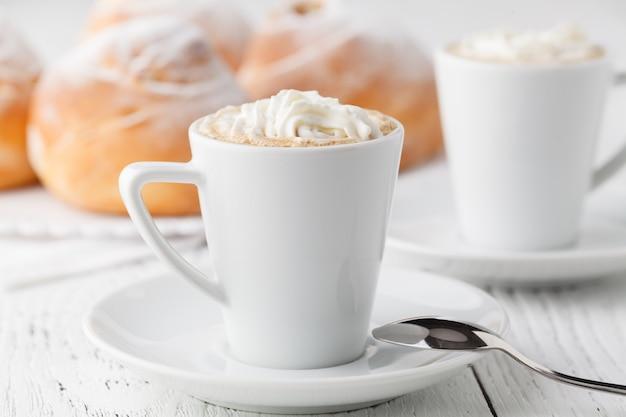 Een gerecht van soesjesroom met een kopje thee of koffie voor een middagpauze.