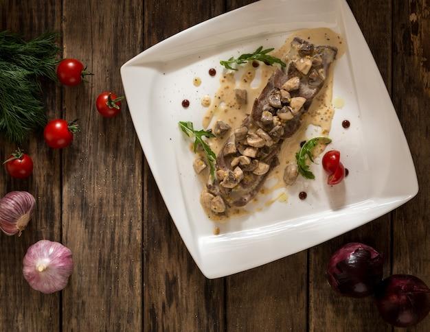 Een gerecht van vlees en champignons gekruid met jus op een vierkant bord, bovenaanzicht
