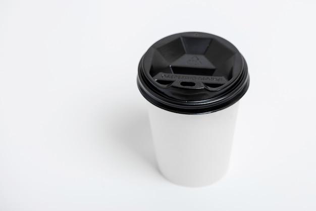 Een gerichte wegnemen witboek beker met zwarte dop gepresenteerd aan de voorkant, geïsoleerd op een eenvoudige grijze achtergrond