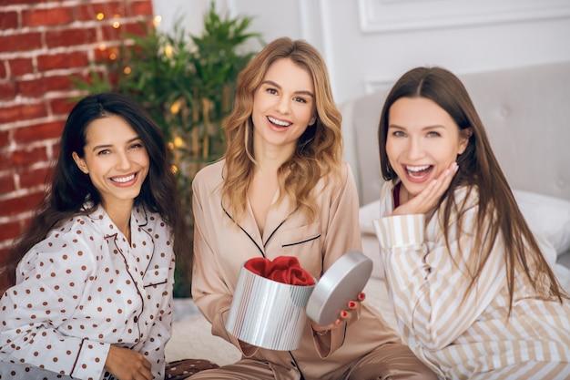 Een geschenk. drie mooie meisjes in pyjama's openen de geschenkdoos en kijken opgewonden